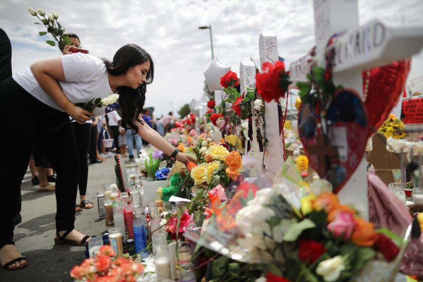 A woman places flowers at a memorial outside the site of the El Paso mass shooting