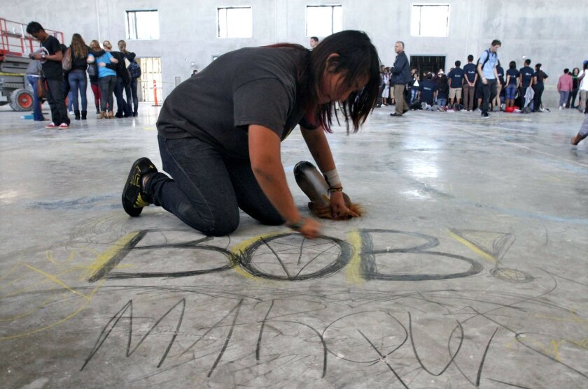 """Senior Marquis Antosh writes """"Bob,"""" her nickname since middle school, on the concrete floor of the new gym under construction on the San Marcos High School campus Monday."""