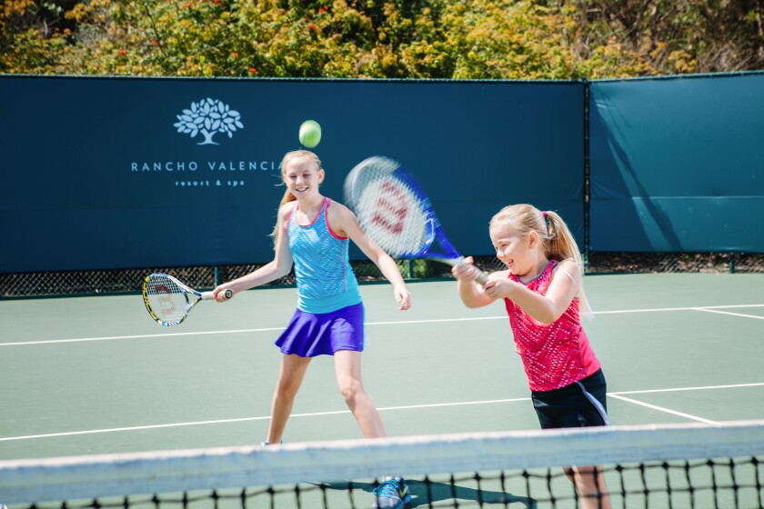 Youth playing tennis at Rancho Valencia Resort & Spa when the courts were open.