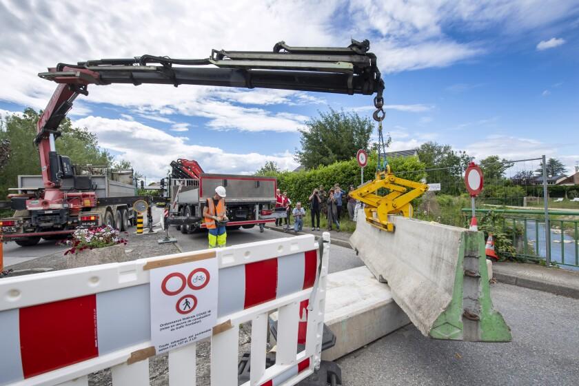 Una grúa retira las barreras de cemento que cerraban un cruce fronterizo en Thonex, cerca de Ginebra, Suiza