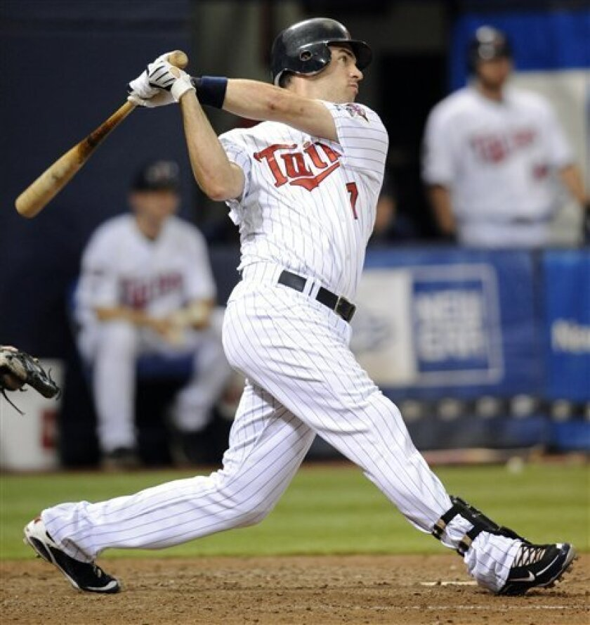 FILE - This is an Aug. 13, 2009, file photo showing Minnesota Twins' Joe Mauer hitting a three-run homer against the Kansas City Royals in the fifth inning of a baseball game in Minneapolis. Mauer has become only the second catcher in 33 years to win the American League Most Valuable Player Award,