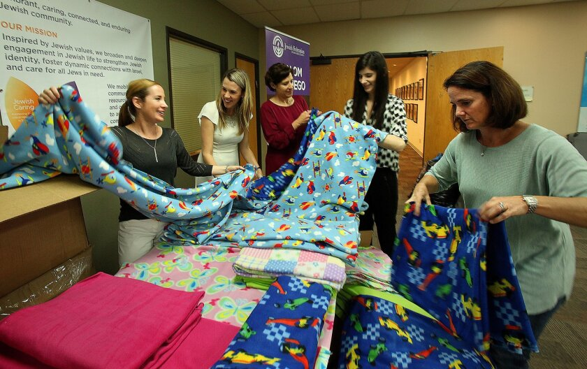 Kara Liederman, left, Jenna Zetisky, Lisa Kalal, Leigha Silberman and Britney Ewing,  fold some of the many quilts created for charities by seniors and teens at the Jewish Federation of San Diego offices. .