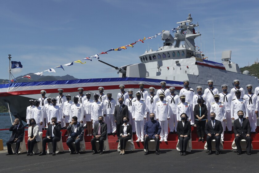 Taiwan's President Tsai Ing-wen, third from right, takes group photo with officers during the commissioning ceremony of the the domestically made Ta Jiang warship at the Suao naval base in Yilan county, Taiwan, Thursday, Sept. 9, 2021. Taiwan's president oversaw the commissioning of the new domestically made navy warship Thursday as part of the island's plan to boost indigenous defense capacity amid heightened tensions with China. (AP Photo/Chiang Ying-ying)