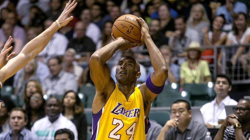 Lakers guard Kobe Bryant (24) attempts a three-point shot against the Jazz in the first quarter of their exhibition game Sunday night in Honolulu.