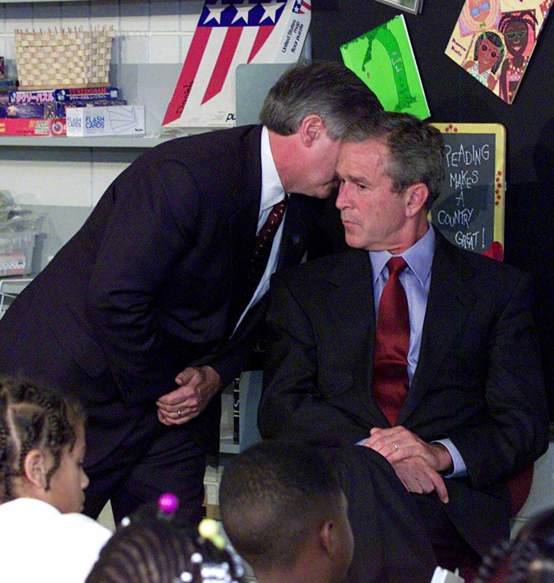 یک دستیار در گوش رئیس جمهور بوش در حالی که در کلاس درس می نشیند نجوا می کند