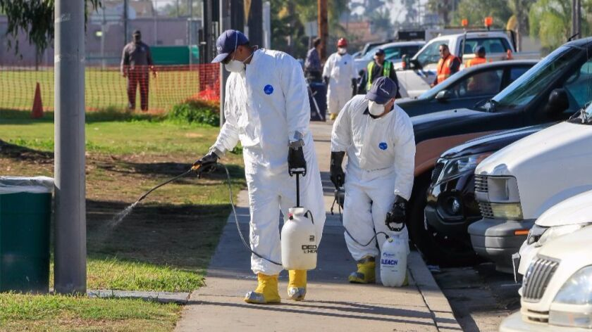 A cleaning crew in North Park sprays an initial high-concentrate bleach solution on a sidewalk by a
