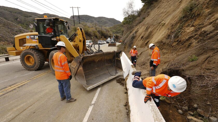 A Cal Trans crew works to place temporary concrete walls (K-rails) on Topanga Canyon Boulevard Monday after large rocks, dirt and debris likely loosened by last week's rainstorm fell onto the pavement, temporarily shutting down the roadway.