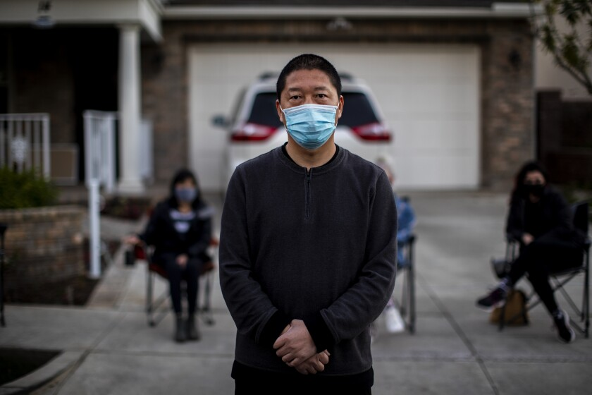 Haijun Si stands in front of his Ladera Ranch family home on Feb. 25 as neighbors gather in a nightly security detail.