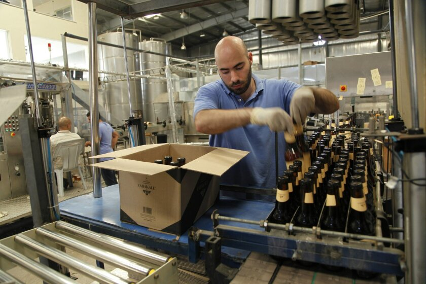 In this Tuesday, Sept. 6, 2016 photo, Carakale Brewery staffer Ramzi Kharoufeh fills a box with beer bottled, pasteurized and labeled that day in Fuheis, Jordan. The maker of Jordan's first craft beer, Carakale, is part of a small but growing group of Arab brewers in the Levant who want to nurture
