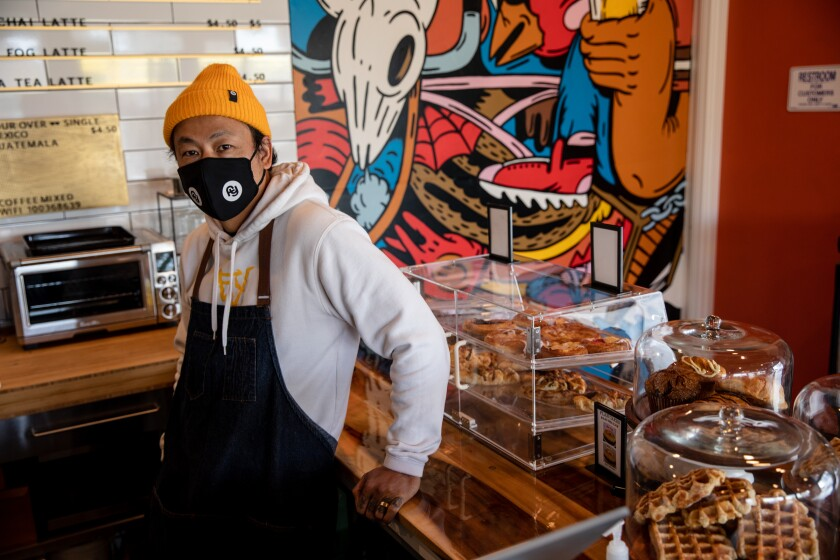 Kwa Nguyen, co-owner of Mixed Grounds coffee shop, stands near artwork in the store Thursday.
