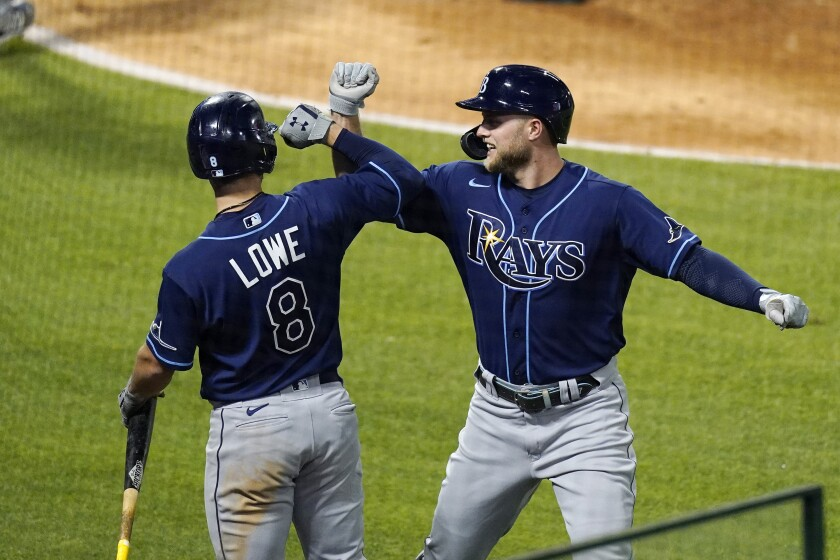 Tampa Bay Rays' Austin Meadows, right, is congratulated by Brandon Lowe hits a solo home run during the seventh inning of a baseball game against the Los Angeles Angels Tuesday, May 4, 2021, in Anaheim, Calif. (AP Photo/Mark J. Terrill)