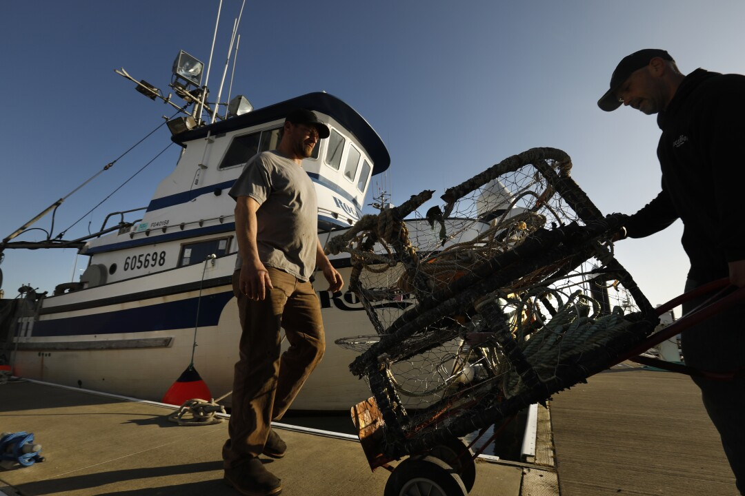 Fishermen move crab pots on the docks in Crescent City marina