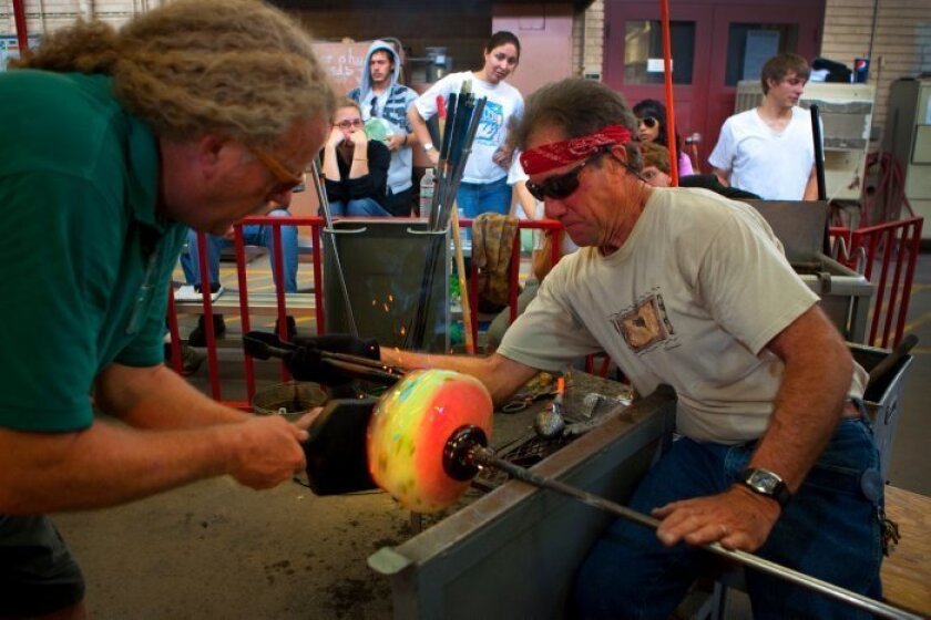 "Garry Cohen shapes glass with the help of John Puroy, assistant lab tech. ""It's kind of like surfing or skateboarding,"" said one student. ""It's just you and the glass."""