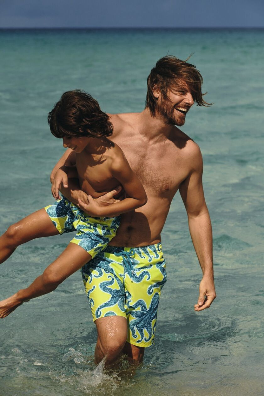 A man and a boy wading in the surf wearing matching yellow swim trunks printed with blue octopuses.