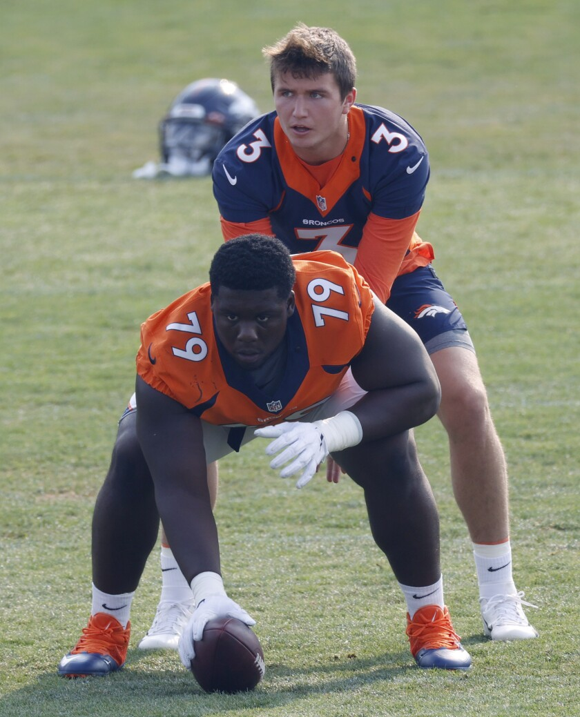 Denver Broncos quarterback Drew Lock, back, takes the snap from center Lloyd Cushenberry III as they take part in drills during an NFL football practice at the team's headquarters Monday, Aug. 24, 2020, in Englewood, Colo. (AP Photo/David Zalubowski)