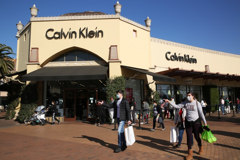 Shoppers wait in line to enter the Calvin Klein store at the Citadel Outlets in Commerce in December.