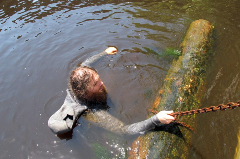 Hewitt Emerson guides a longleaf pine log to a barge after diving to the bottom of the Edisto River in South Carolina.