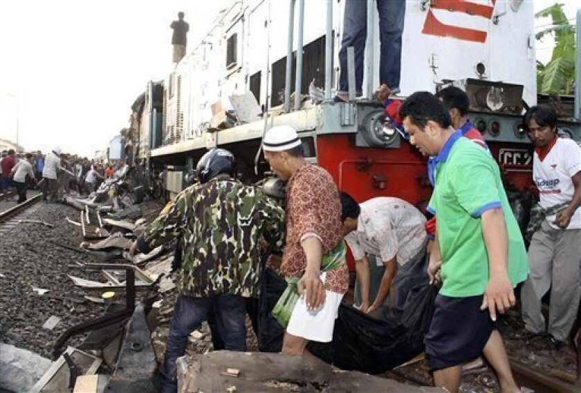 Rescuers carry the body of a victim of a train crash near a station in Petarukan, Central Java, Indonesia, Saturday, Oct. 2, 2010. The early morning train crash in central Indonesia killed dozens of people and injured another dozens, many of them critically, officials and witnesses said. (AP Photo)
