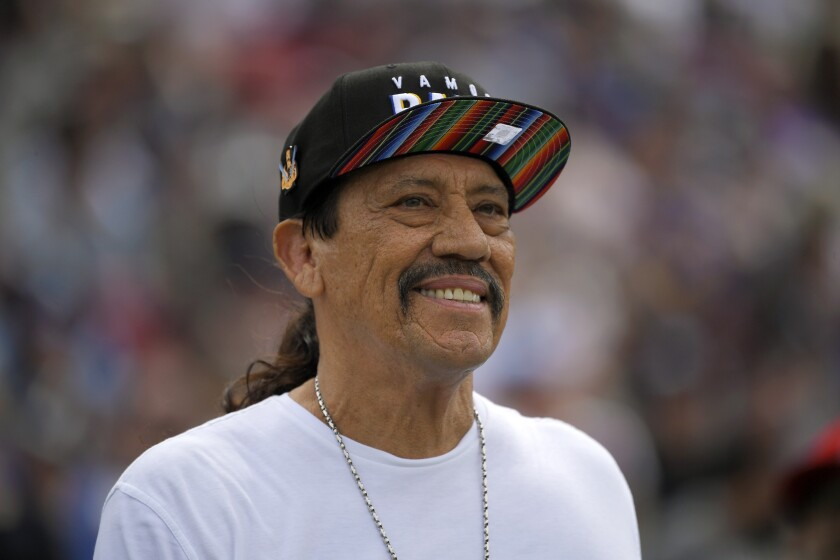 Danny Trejo smiling in a rainbow hat and white shirt.