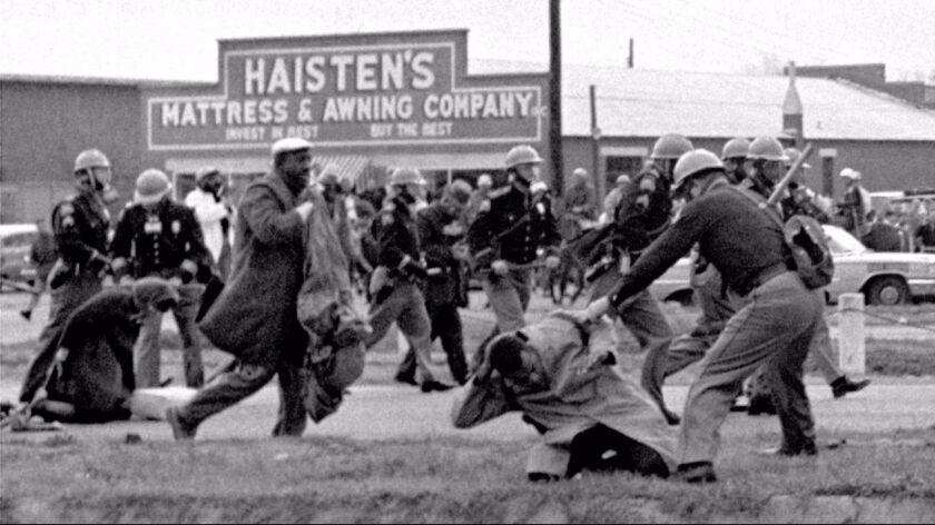 A young John Lewis is seen in the foreground being clubbed by a state trooper during a civil rights protest in Selma, Ala., in 1965.