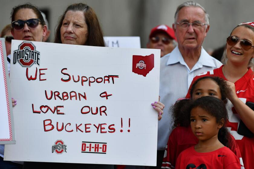 Supporters of Ohio State football coach Urban Meyer hold a rally at the university on Aug. 6.