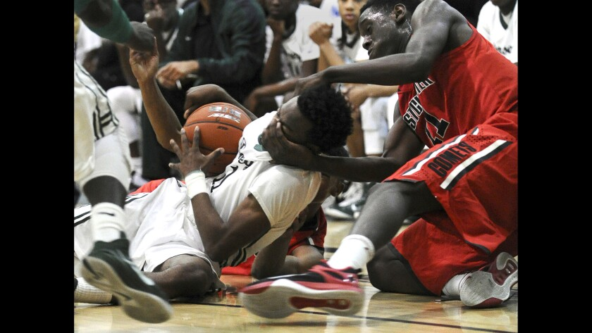 Westchester's L.T. Taylor grabs the face of Dorsey's Albert Allison while battling for a loose ball in the City Open Division semifinal game at Roybal High School on Saturday.