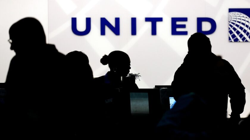 FILE - In this Saturday, Dec. 21, 2013, file photo, travelers check in at the United Airlines ticket