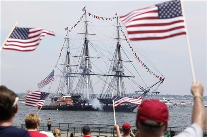 Spectators wave flags as the USS Constitution fires its cannons off Castle Island in Boston on its annual 4th of July turn around in Boston Harbor, Monday, July 4, 2011. (AP Photo/Michael Dwyer)
