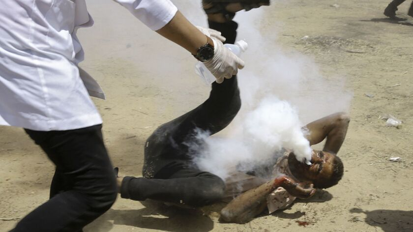 A Palestinian medic rushes to help a protester who was shot in the face with a teargas canister fire