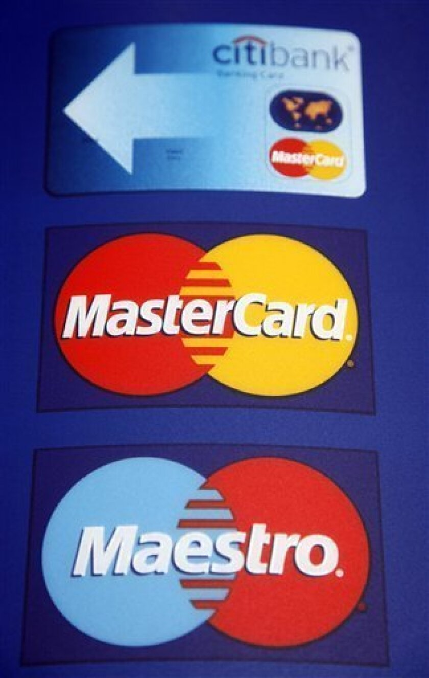 FILE - In this June 23, 2010 file photo, signs for a Citibank banking card, top, a MasterCard credit card, center, and Maestro, bottom, are displayed, in New York. MasterCard Inc. said Tuesday, Nov. 2, 2010, spending on plastic overseas helped lift its third-quarter profit 15 percent.(AP Photo/Mark Lennihan, file)