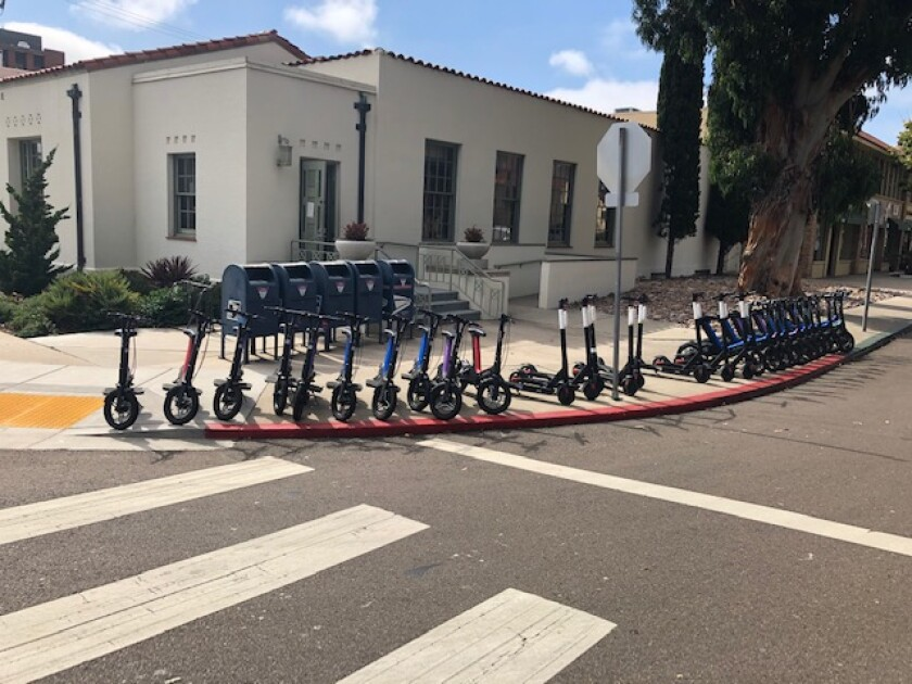 Electric devices are stationed recently outside the Wall Street post office in La Jolla in violation of city staging rules.