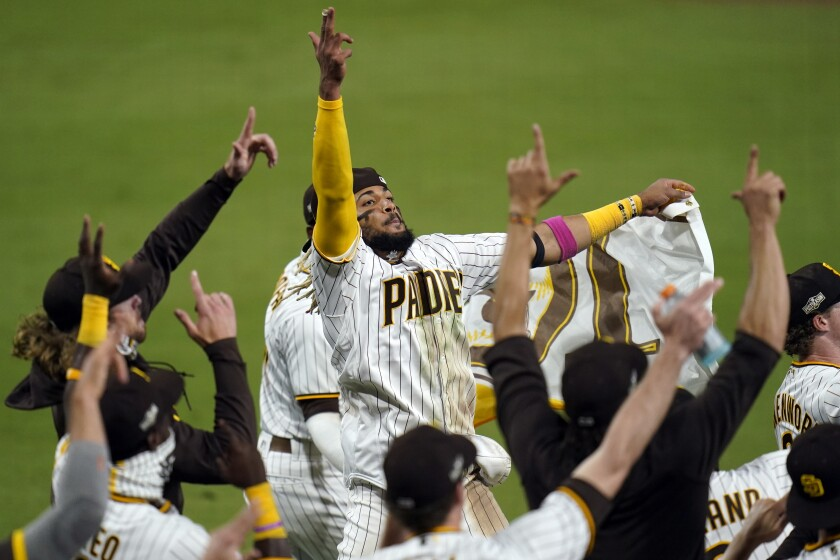 San Diego Padres' Fernando Tatis Jr., center, celebrates with teammates after the Padres defeated the St. Louis Cardinals 4-0 in Game 3 of a National League wild-card baseball series Friday, Oct. 2, 2020, in San Diego. The Padres won the series and advanced to the Division Series. (AP Photo/Gregory Bull)