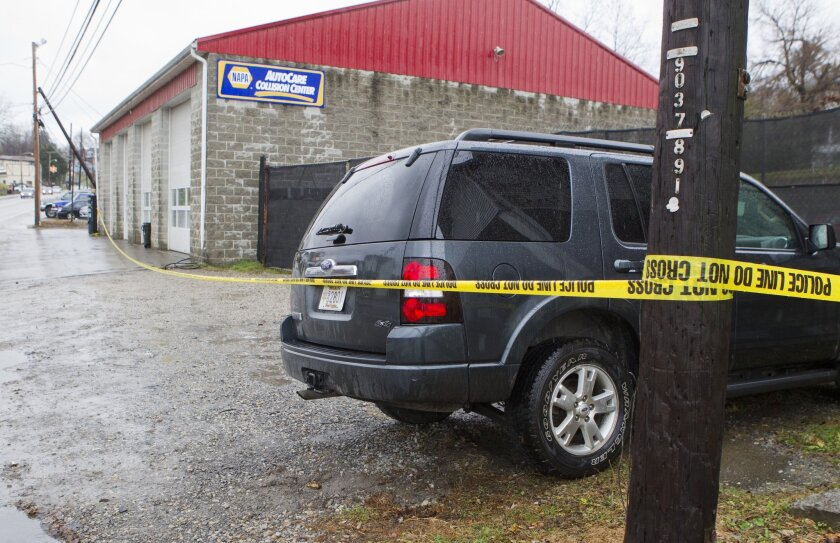 Doug's Towing in Westover, W.Va., is surrounded by police tape Monday after its owner was fatally shot by a rival who also killed three other people, authorities said.