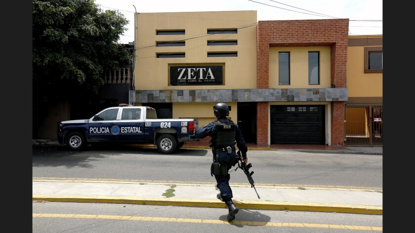 Baja California state police stand guard outside the offices of Tijuana's Zeta newspaper, a weekly i