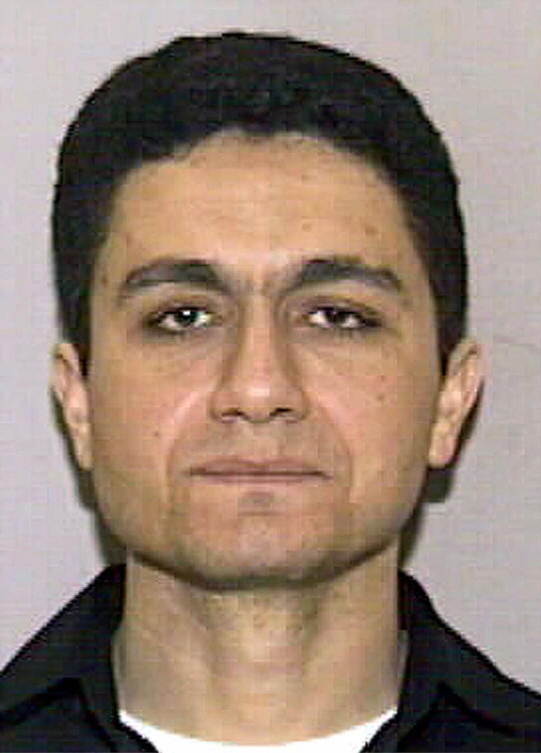 A man with dark hair and dark eyes in a black shirt