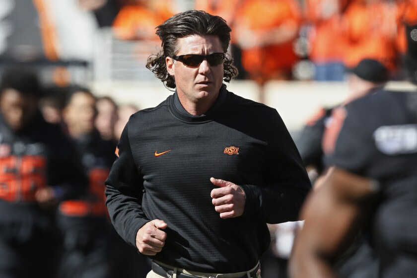 Oklahoma State head coach Mike Gundy runs onto the field.