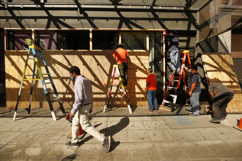 Workmen on ladders erect a plywood wall at a downtown L.A. storefront.