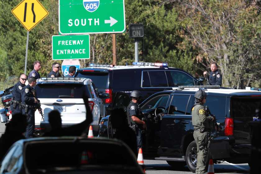 Law enforcement personnel stage near the Katella Avenue onramp to the 605 Freeway in Los Alamitos.