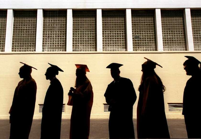 Students in caps and gowns line up at a high school graduation.