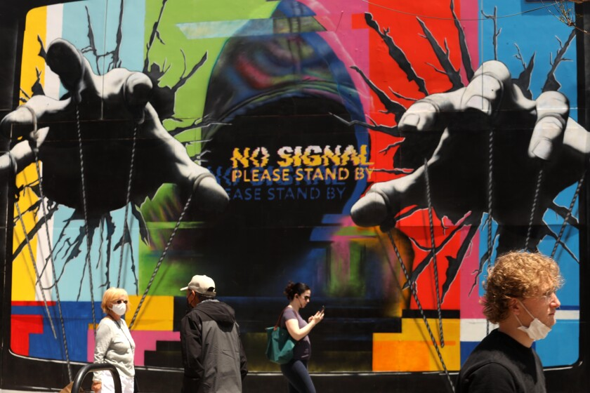 Visitors, some wearing masks, walk past a mural by artist Hijack while visiting the Third Street Promenade.