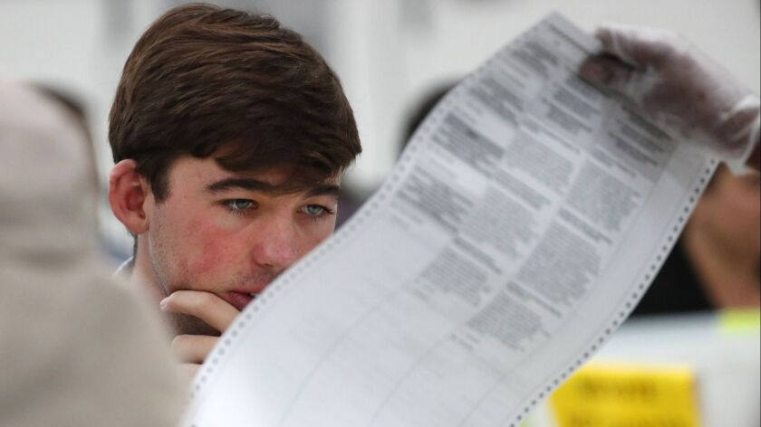 FILE- In this Friday, Nov. 16, 2018, file photo a Republican observer looks at a ballot during a han
