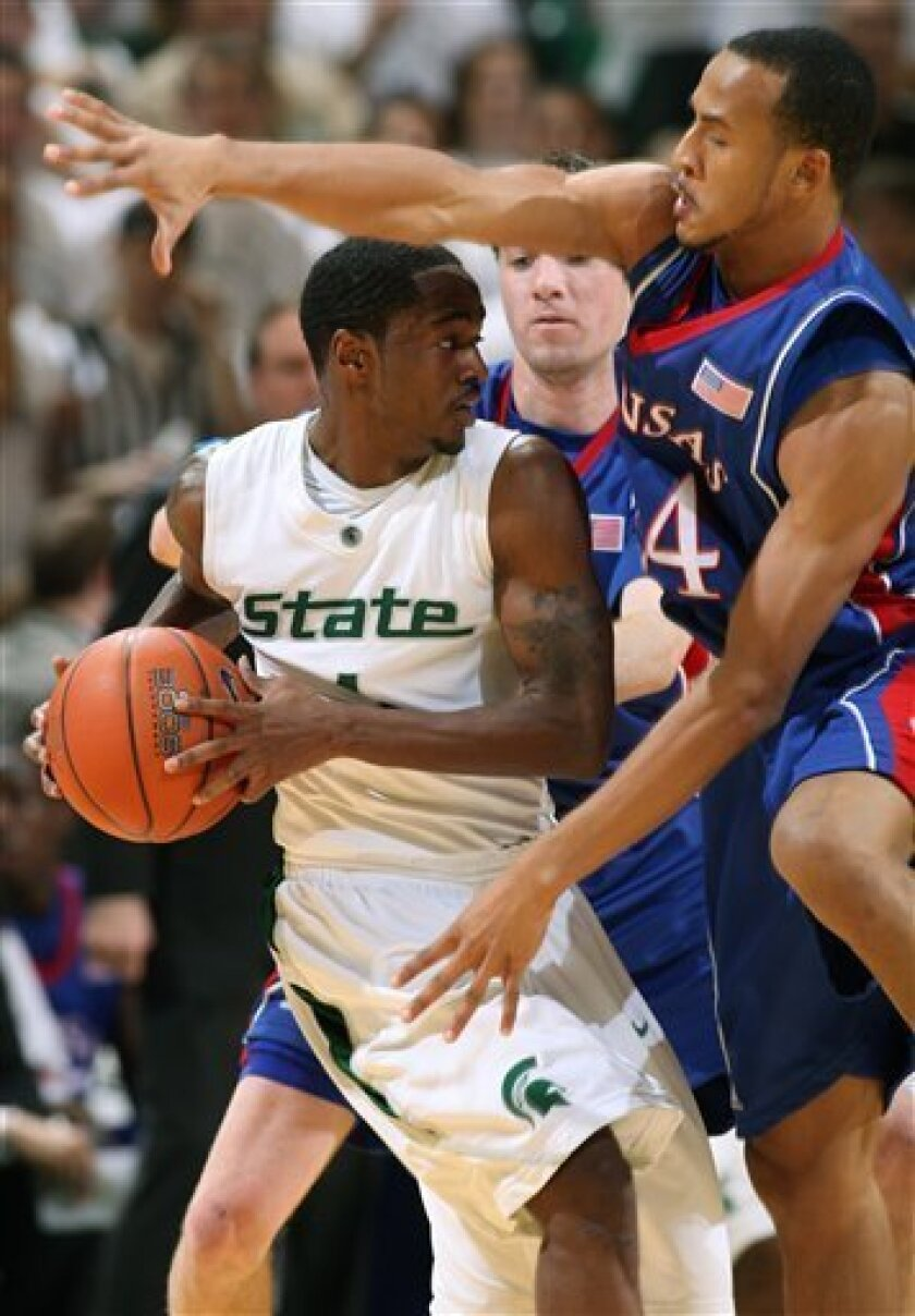 Michigan State's Kalin Lucas, left, is pressured by Kansas' Travis Releford, right, and Brady Morningstar, rear, during the first half of an NCAA college basketball game Saturday, Jan. 10, 2009, in East Lansing, Mich. (AP Photo/Al Goldis)