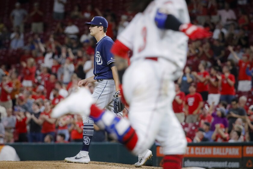 Padres starting pitcher Cal Quantrill (left) walks up the mound after giving up a two-run home run to Cincinnati's Freddy Galvis (right), during the sixth inning of Tuesday's game.