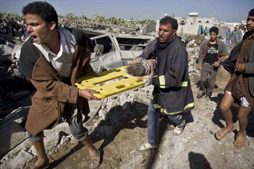 Men carry the body of a child they uncovered from rubble of houses destroyed by Saudi airstrikes near Sana Airport in Yemen on March 26.