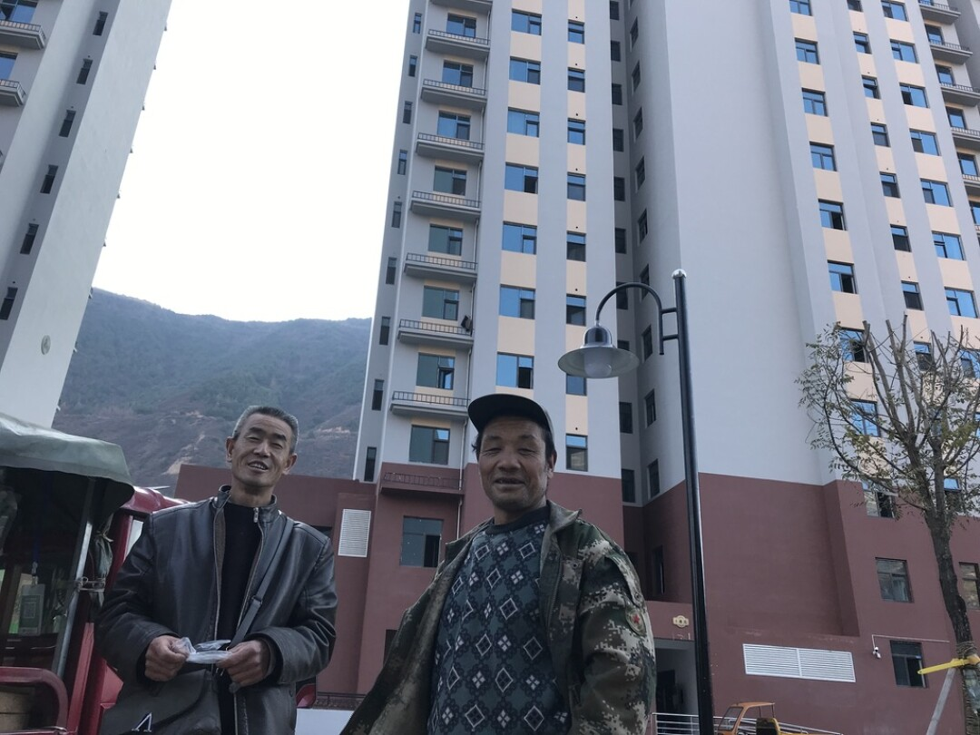 Villagers relocated from Lianghekou village stand outside the new high-rises where they now live.