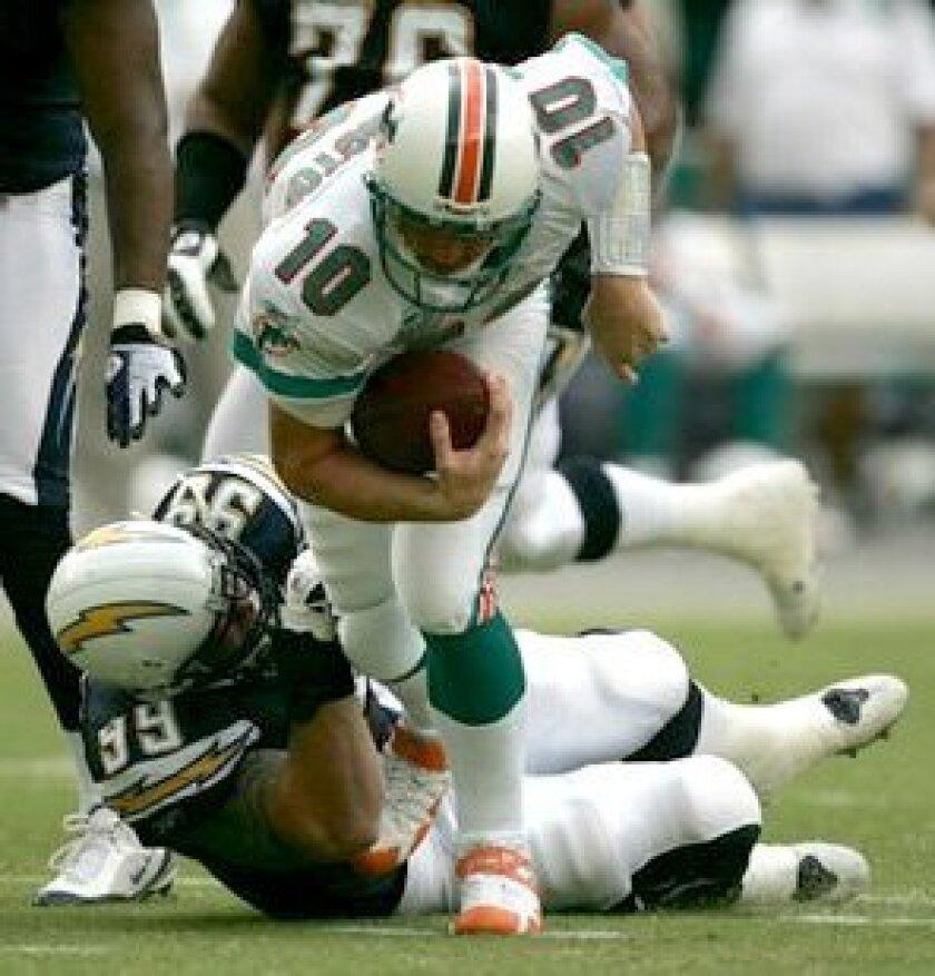 Miami's Chad Pennington is taken down by San Diego's Igor Olshansky in the second quarter.<br><em>Sean M. Haffey/Union-Tribune</em>