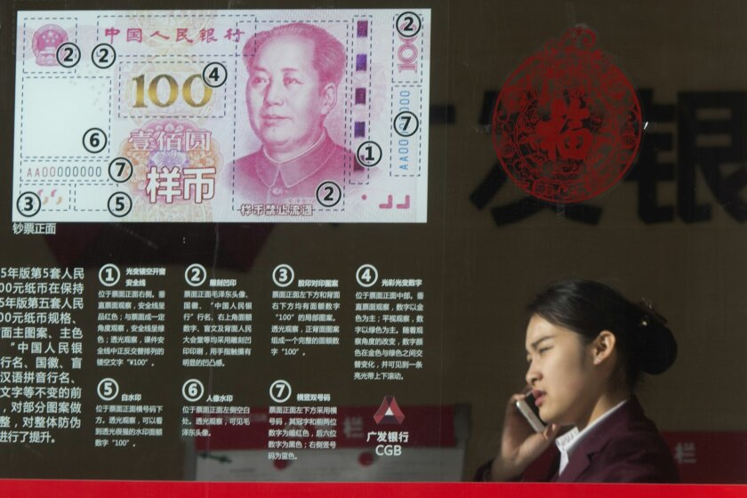 FILE - In this Feb. 16, 2016 file photo, a woman speaks on her phone near a display highlighting the new Chinese bank notes at a bank in Beijing, China. The Chinese economy is littered with companies that can't pay their bills and survive only with financial help from the government. These companies and their debts pose another threat to an economy squeezed by five years of slowing growth, a free-fall in its currency and a stock market that's sunk 20 percent this year.(AP Photo/Ng Han Guan)