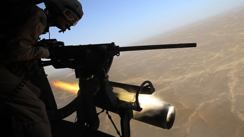 Staff Sgt. Robert Wise takes a run down the firing range on Saturday as high-explosive rockets are launched from a heavily armed Huey helicopter in southwestern Afghanistan.
