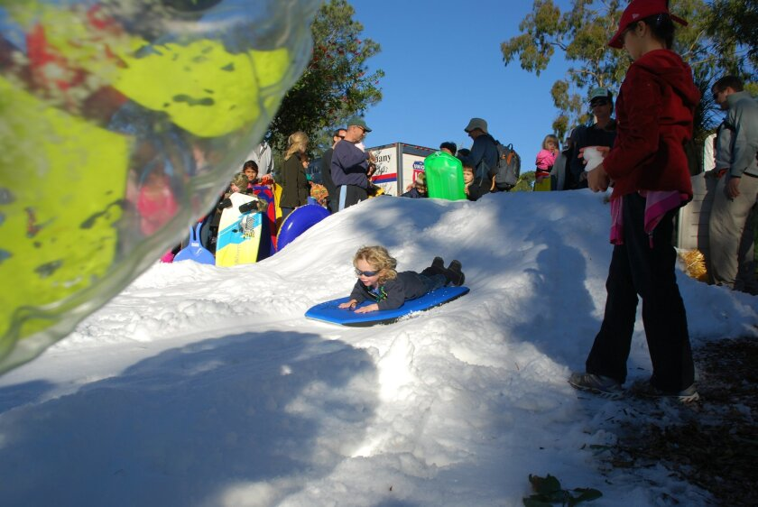 A girl slides down a snowy hill at the San Diego Botanic Garden's festival of Lights. This year's fest kicks off Dec. 7. Photo courtesy of Becky Reeb