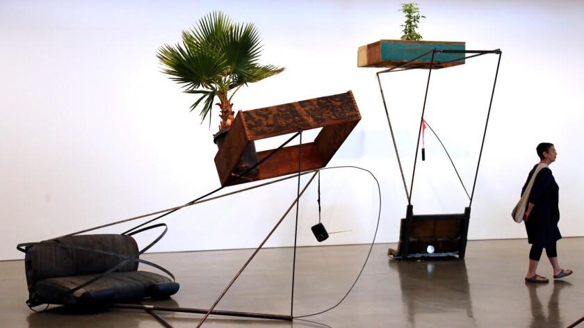 "A visitor walks past two pieces by Mexican artist Abraham Cruzvillegas: ""Autoconcancion V,"" left, and ""Autoconcancion I."""